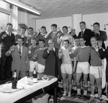 The Everton team celebrate after claiming the League Division One championship. Everton chairman John Moores (centre) and manager Harry Catterick (left, wearing suit) join in the celebrations